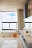 Spacious designer bathroom with freestanding white bathtub below panoramic window, twin sinks and mirrored wall cabinet