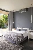 Elegant double bed with grey upholstery against dark grey wall and between two white, designer pendant lamps; view of planted terrace