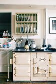 Kettle on vintage-style AGA cooker and plate rack on wall in renovated industrial building