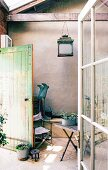 Porch with exposed beams, vintage lantern, garden furniture and plants in zinc containers in vintage interior