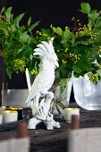White china cockatoo ornament in front of glass vase of green leaves on rustic table
