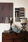 Glass vase and various artistic, African accessories on antique chest of drawers below graphic artworks on wall