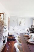 Rustic wooden table, white upholstered chair, sleeping area and natural finds on wall