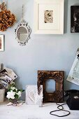 Photo in white frame and mirror on wall above gilt wooden frame and various vintage items on rustic wooden table