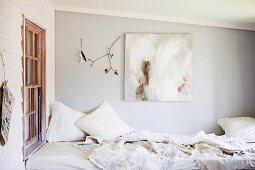 Various white blankets and cushions on daybed in corner next to window and below picture and natural finds on wall painted pale grey