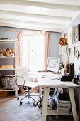 PC and office materials on white-painted wooden table, white leather modern swivel chair and white wood-beamed ceiling in room painted pale grey