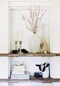 Vases, candlesticks and books on rustic wooden shelves built into niche with white-painted wooden back wall