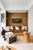 Comfortable wood-clad niche with fitted sofa and collection of cushions behind armchair in lounge area