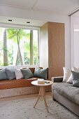 Delicate round side table, sand-coloured sofa in front of fitted cupboard with integrated window seat and view of palm tree trunks in garden