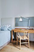 Designer lamp, wooden chair, desk and single bed in simple, minimalist stylish interior