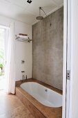 Concrete wall, rainfall shower and sunken white bathtub with stone-tiled surround in minimalist bathroom