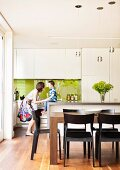 Cheerful child and mother in front of white designer kitchen with lime green reflective splashback in open-plan interior