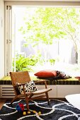 Comfortable retro wooden armchair on graphic black and white rug, open glass wall and view into green sunny garden