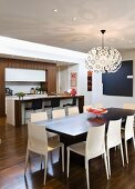 Dining table, designer Dandelion pendant lamp and pale plastic chairs in front of breakfast bar in open-plan kitchen