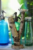Glass candle holders on forked birch branch, vintage bottles and soda siphons