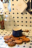 Trivet made from discs of wood on kitchen counter tiled in vintage pattern