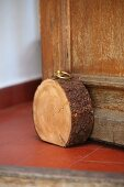 Rustic doorstop made from slice of tree trunk with straightened bottom edge and brass ring screwed into top