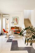 Arc lamp above tulip dining set with orange chair cushions next to masonry staircase