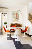 Tulip dining set with orange chair cushions combined with classic arc lamp and small, antique cabinet