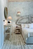 French bed with antique headboard against white, half-height panelling; blue-grey vintage effect walls and worn wooden floor