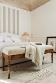 Knitted blanket on upholstered bench at foot of French bed and grey and white pattern of stripes on wall