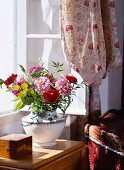 Ceramic vase of garden flowers in sunlight in front of open lattice window with draped curtain