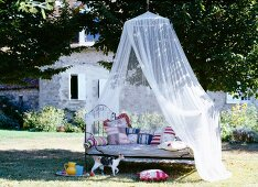 Iron bed with patterned, handmade scatter cushions below draped mosquito net in garden of French country house