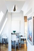 Tall dining counter and bar stools in converted attic with contemporary ceiling light in foreground