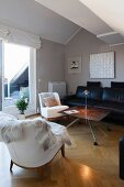 Fur blanket on white armchair and black leather sofa around DIY coffee table in attic interior with view of balcony