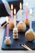 Lit candles in candlesticks made from wooden balls on slate slab