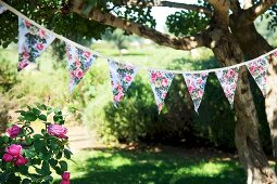Floral bunting strung between trees in garden