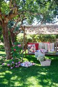 Different patterned scatter cushions on rustic garden swing seat under shady tree with picnic basket on ground
