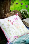 Floral cushion and picnic basket against tree trunk