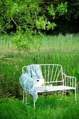 Delicate, white metal garden bench with blanket and seat cushion in meadow in rural surroundings