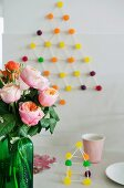 Stylised Christmas tree and gingerbread house made from toothpicks and sweeties; roses in green bottle in foreground
