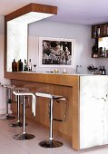 Designer bar stools at wood-clad counter and Corian worksurface in open-plan kitchen
