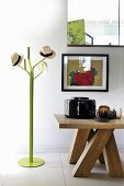 Various hats on green coat stand next to solid wooden table with various vases below framed picture on wall