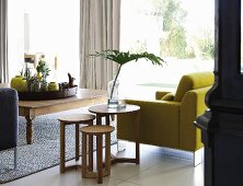 Set of wooden side tables next to yellow armchair, tray and various yellow vases on rustic wooden coffee table and view into garden through glass wall