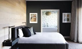 Double bed with pillows stacked against upholstered headboard against wood-clad wall in elegant bedroom with view into ensuite bathroom through open doorway
