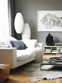 Corner of modern, grey-painted living room with white sofa and cushions, classic Bubble Cigar pendant lamps and modern artwork on wall