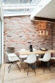 White shell chairs at dining table on wooden floor surrounded by exposed brickwork and modern conservatory glazing