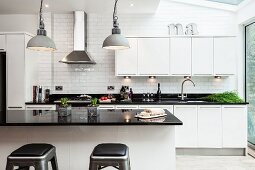 Island counter with black, glossy worksurface in open-plan designer fitted kitchen with white fronts