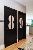 Enormous numbers on black-painted doors in open-plan hallway
