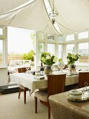 Set table below white awnings on ceiling in elegant conservatory with open terrace doors