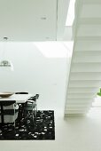 Black and white designer dining area next to bottom view of white, free-standing staircase