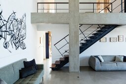 Dark blue steel staircase behind concrete cross in open-plan loft interior with grey sofas and graffiti-style mural