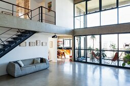 Open-plan interior of concrete-framed building with steel staircase and polished concrete floor; roofed terrace behind two-storey glass facade