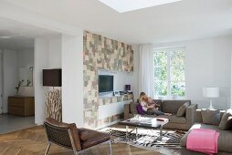 Modern sofa set and zebra-skin rug in front of media cabinet with patchwork fronts in open-plan interior; mother and toddler on sofa