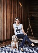Woman sitting on bench and dog on rug with geometric pattern in front of wooden wall