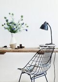 Black, 60s-style, metal wire chair in front of table with simple wooden top and white vase of Nigella damascena
